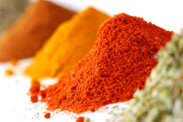 Colorful spice piles on a bench.